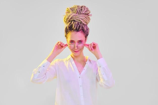 Vrouw in witte blouse met dreadlocks houdt de strik van de bril met beide handen vast
