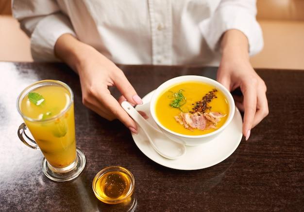 Vrouw in witte blouse smakelijke maaltijd bestellen bij restaurant.