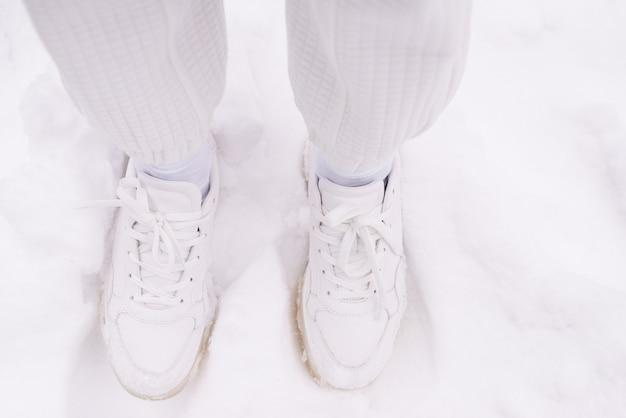 Vrouw in witte broek en witte sneakers staat in een sneeuw.