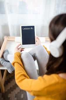 Vrouw in witte draadloze hoofdtelefoons houdt witte tablet met pen. thuiskantoor terwijl u zelf isoleert, thuiswerkend. online onderwijs, e-learning tijdens quarantaine.