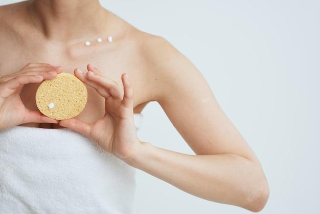 Vrouw in witte handdoek blote schouders schone huid na douche close-up.