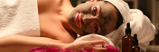 Vrouw in witte handdoek met masker op haar gezicht aromatherapie procedures met oliën.