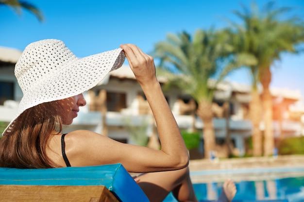Vrouw in witte hoed die op een lanterfanter dichtbij het zwembad bij het hotel ligt