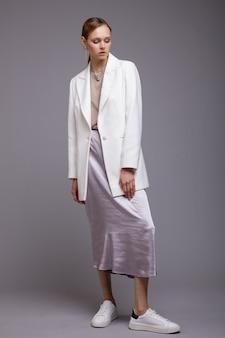 Vrouw in witte jas lange metallic zilveren rok sneakers grijze achtergrond studio shot portret