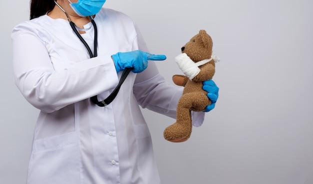 Vrouw in witte jas met knopen die een bruine teddybeer met een wit gaasverband vastgebonden met haar poot