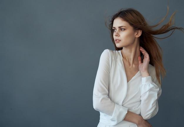 Vrouw in witte jurk aantrekkelijke look luxe model grijze achtergrond