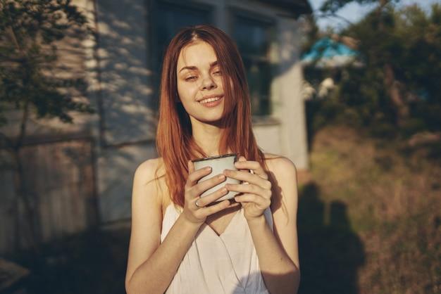 Vrouw in witte jurk buiten zomer landhuis