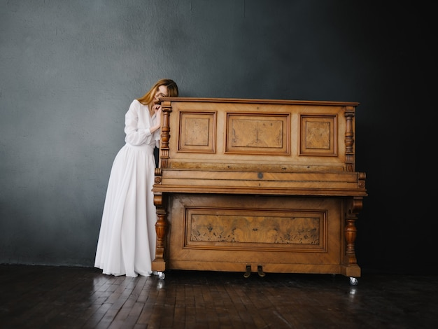 Vrouw in witte jurk charme poseren piano interieur