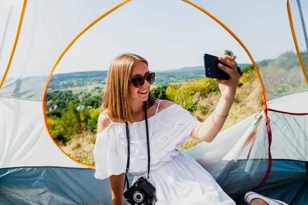 Vrouw in witte jurk die een selfie in een tent neemt