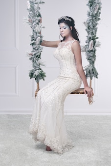 Vrouw in witte jurk en ijzige make-up op schommel