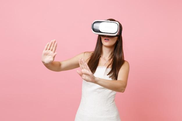 Vrouw in witte jurk, headset van virtual reality raak iets aan als een druk op de knop of wijzend naar een zwevend virtueel scherm
