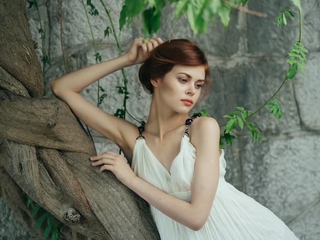 Vrouw in witte jurk in de buurt van boombaserende stenen muur griekenland