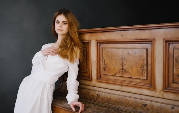 Vrouw in witte jurk in de buurt van piano luxe charme klassieke stijl