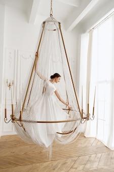 Vrouw in witte jurk in een kroonluchter in een lichte kamer