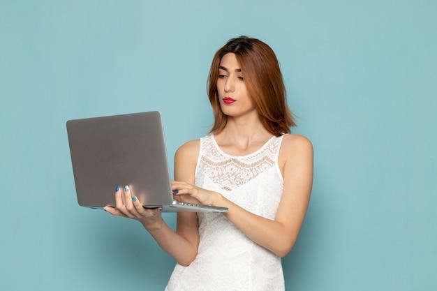 Vrouw in witte jurk met behulp van laptop
