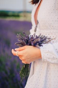 Vrouw in witte jurk met boeket lavendel bloemen close-up