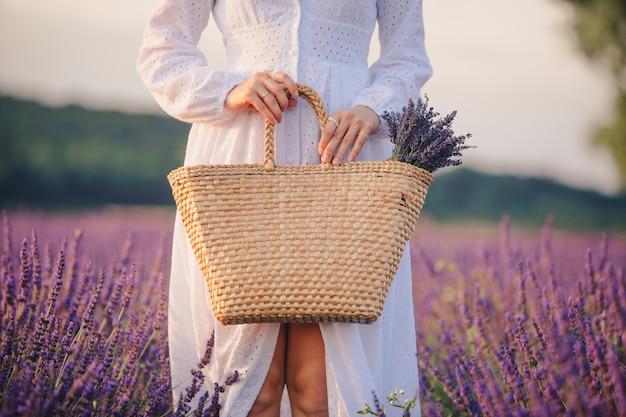 Vrouw in witte jurk met boeket lavendel bloemen in strozak close-up