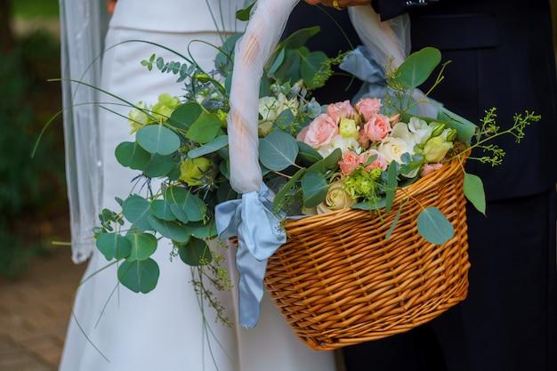 Vrouw in witte jurk met een mand met bloemen geen gezicht