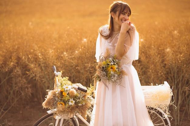 Vrouw in witte jurk met fiets in veld