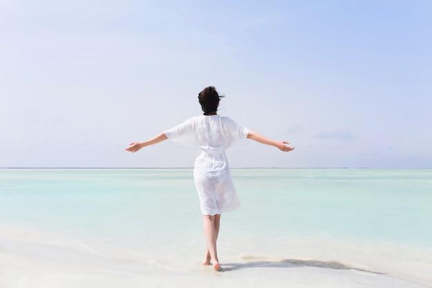 Vrouw in witte jurk met opgeheven handen