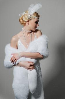 Vrouw in witte jurk met schouderbanden en lange bontstola