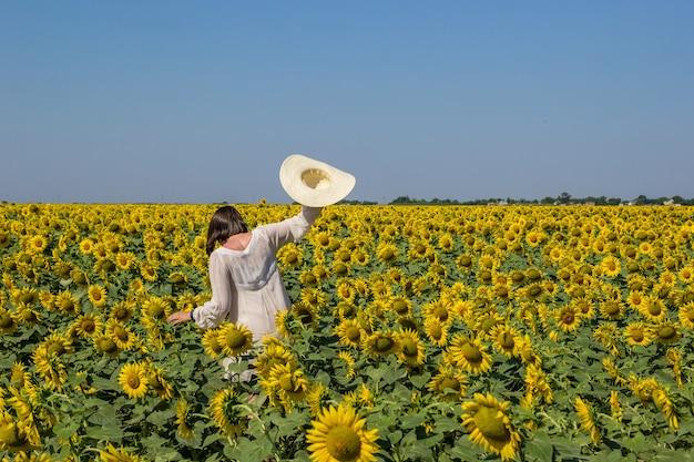 Vrouw in witte jurk met strohoed gaat op het gebied van bloeiende gele zonnebloemen.