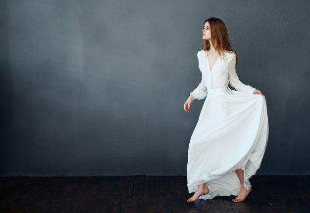 Vrouw in witte jurk op blote voeten dans plezier donkere achtergrond