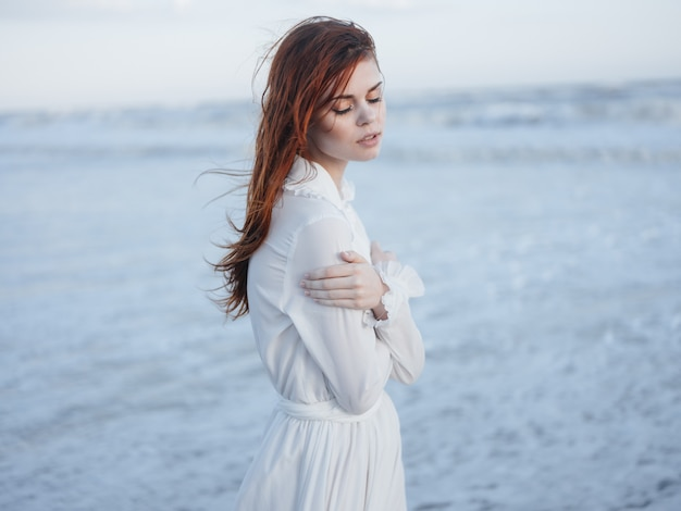 Vrouw in witte jurk op de aard van het strand van de golven van de oceaan