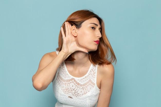 Vrouw in witte jurk poseren en proberen te horen