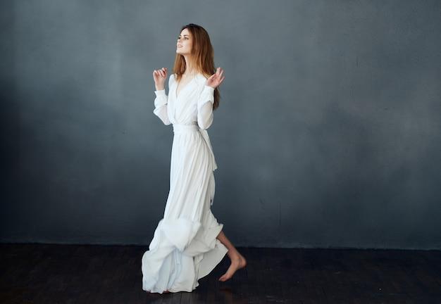 Vrouw in witte jurk poseren op een donkere achtergrond op blote voeten in volle groei