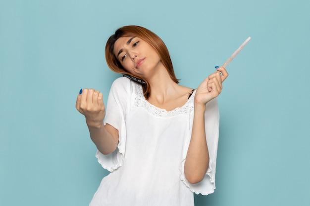 Vrouw in witte jurk tot vaststelling van haar nagels en praten over de telefoon