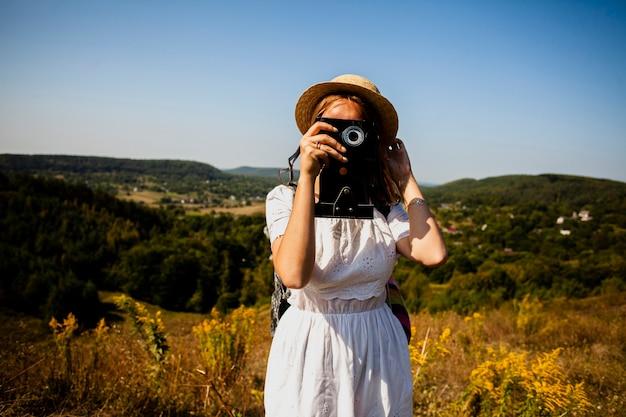 Vrouw in witte kleding die een foto van camera neemt