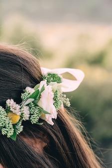 Vrouw in witte kleding die zich op gebied bevindt dat bloemkroon draagt. jonge bos geïnspireerde bruid
