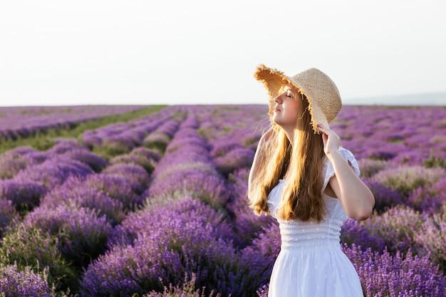 Vrouw in witte kleding en strohoed op lavendelgebied