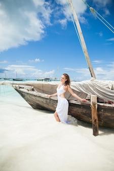 Vrouw in witte kleding op de oceaanachtergrond met vissersboot