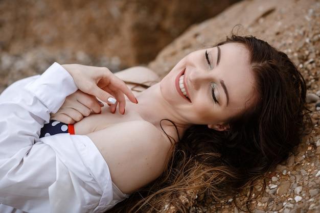 Vrouw in witte kleding verfrissend aan zee.