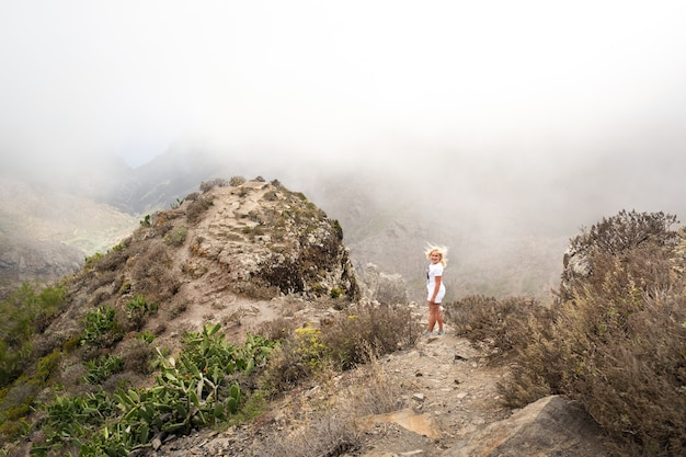 Vrouw in witte kleren klimt naar de top van een klif op het eiland tenerife, spanje