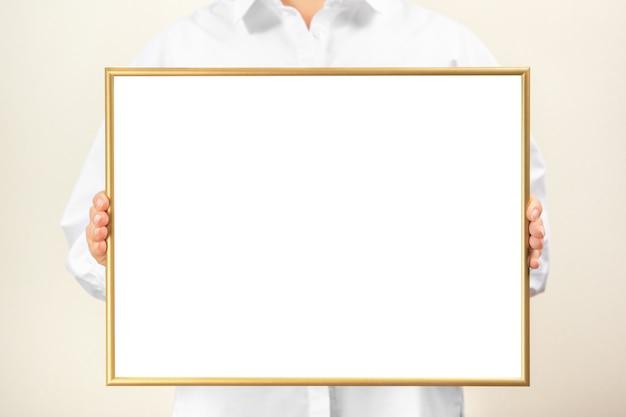 Vrouw in witte kleren toont een leeg mockup-frame