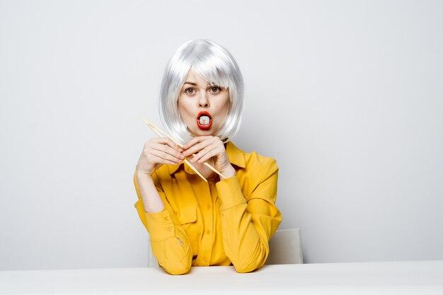 Vrouw in witte pruik eet sushibroodjes