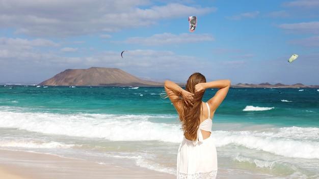 Vrouw in witte sundress op zoek kitesurfing mensen corralejo dunes beach, fuerteventura, canarische eilanden