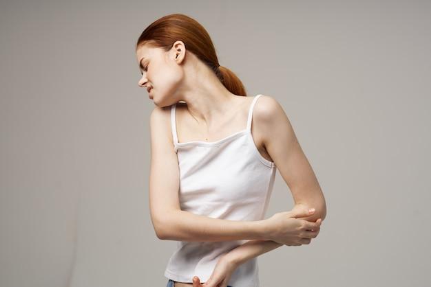 Vrouw in witte t-shirt elleboog pijn artritis chronische ziekte lichte achtergrond