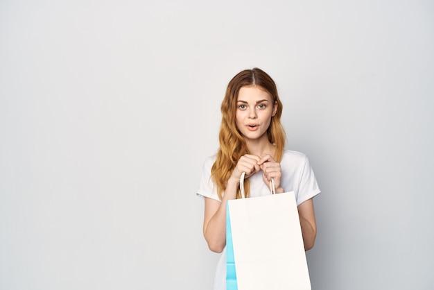 Vrouw in witte t-shirt met pakketten in handen winkelen winkel