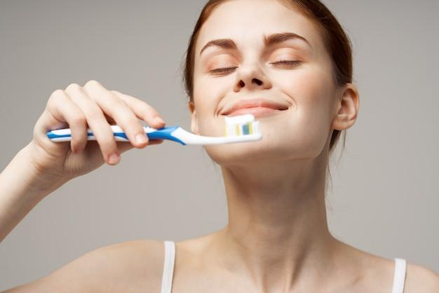 Vrouw in witte t-shirt reinigt tanden hygiëne levensstijl