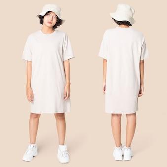 Vrouw in witte t-shirtjurk en emmerhoed vrijetijdskleding