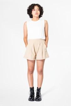 Vrouw in witte tanktop en beige korte broek met zomerkleding met designruimte
