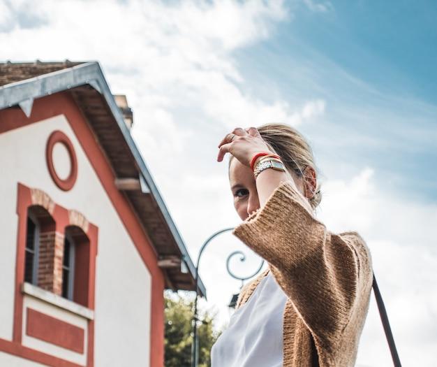 Vrouw in witte top en bruin vest buitenshuis