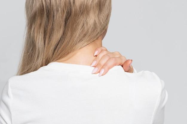 Vrouw in witte top met pijn in haar nek en rug.