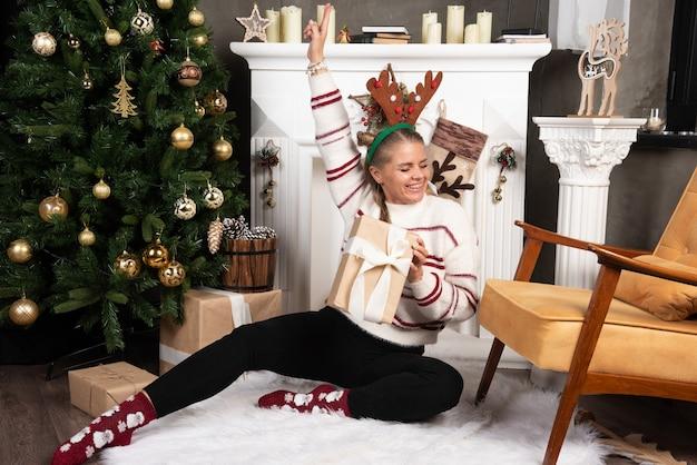 Vrouw in witte trui die zich gelukkig voelt in het interieur van kerstmis.