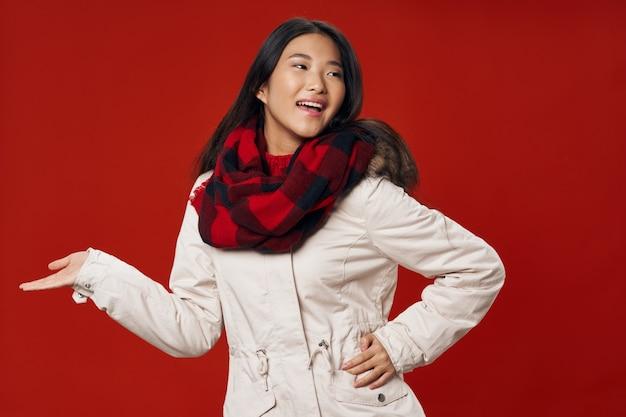 Vrouw in witte winterjas ballen tellen cool winter lifestyle rode achtergrond