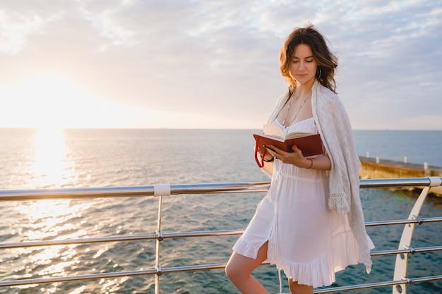 Vrouw in witte zomerjurk wandelen aan zee op zonsopgang met dagboek boek in romantische stemming denken en notities maken